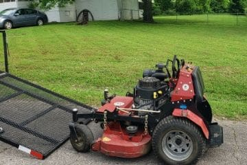 A large lawn mower being lowered from a trailer.