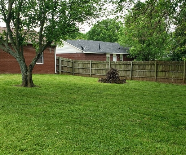 The backyard of a client of Riverview Turfworks in Van Buren AR. The grass is green and healthy and has been prefessionally cut.