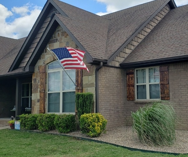 A home in Van Buren that has been serviced by Riverview Turfworks. The grass has been mowed, and the landscape beds around the front door have fresh mulch and pruned shrubs.