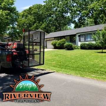 A Riverview Turfworks truck hauling a large zero turn lawn mower sitting in front of a lawn ready to be mowed.