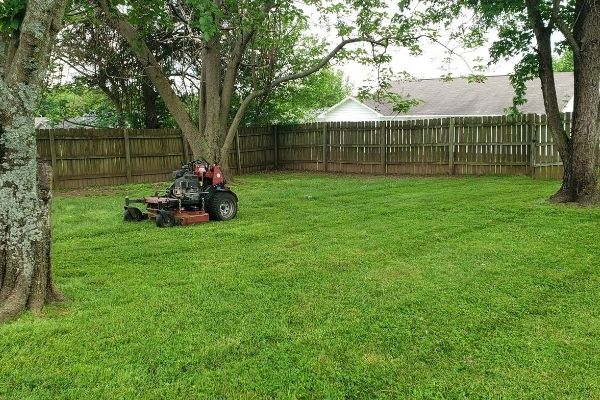 A large commercial lawn mower sitting in a fenced in back lawn during a grass cutting service.
