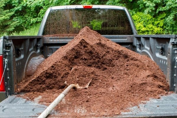 A large pile of brown mulch in the back of a Riverview Turfworks' truck.