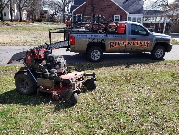 A large zero turn lawn mower sitting in grass. In the background is a Riverview Turfworks work truck.