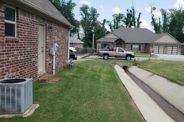 A residential home with a side yard that has been recently and neatly mowed. In the far background, there is a Riverview Turfworks truck parked on the curb.