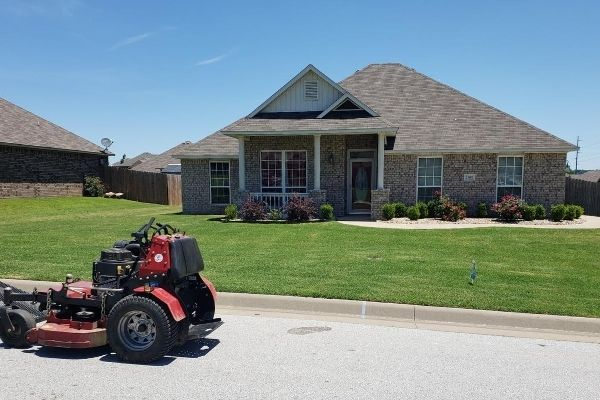 A large commercial mower ready to be loaded back into the truck. In the background is a client's home with a freshly mowed lawn.