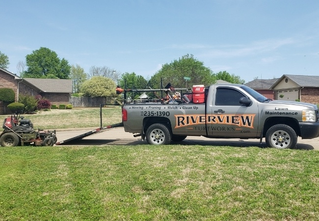 A lawn mower being unloaded from a Riverview Turfworks work truck.