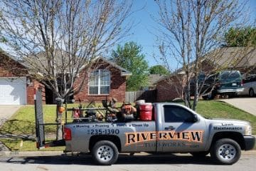 A work truck baring Riverview Turfworks logo and phone number parked in front of a home they are about to service.
